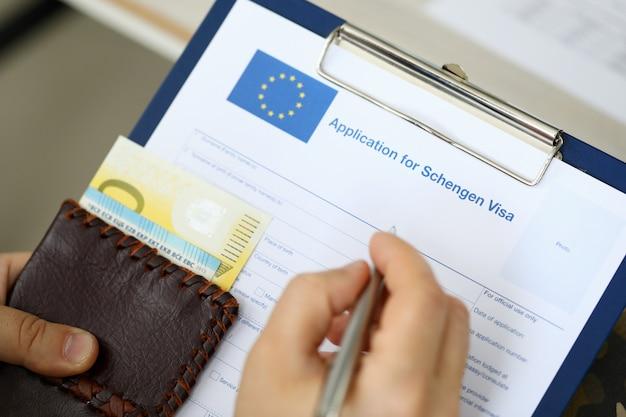 Bovenaanzicht van man invullen van documenten voor schengen-visum terwijl geld vast te houden. reizen concept