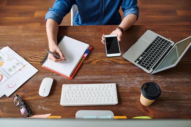 Bovenaanzicht van manager zittend door houten tafel, notities maken in notitieblok en moderne gadgets gebruiken tijdens het werken