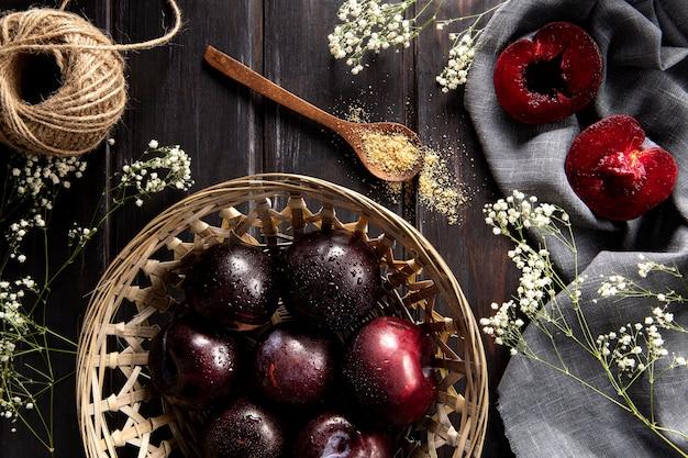 Bovenaanzicht van mand fruit met string en bloemen