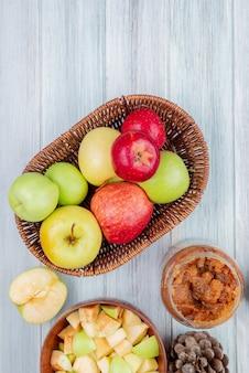 Bovenaanzicht van mand met appels met pot van appeljam kom van appelblokjes half gesneden appel en dennenappel op houten tafel