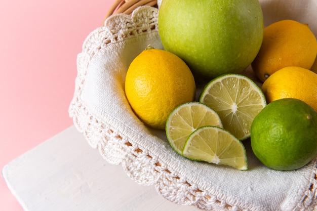 Bovenaanzicht van mand met citrusvruchten, citroenen en limoenen (lemmetjes) binnen op roze oppervlak