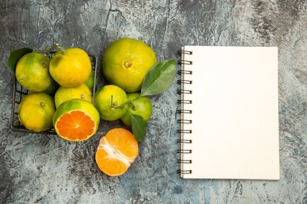Bovenaanzicht van mand met verse groene mandarijnen in tweeën gesneden en gepelde mandarijn naast notebook op grijze achtergrond