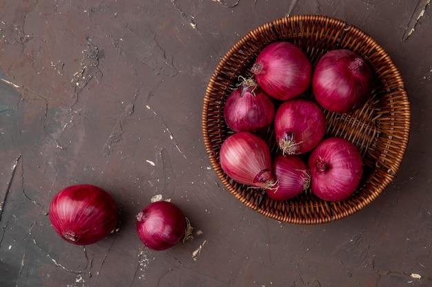 Bovenaanzicht van mand vol rode uien op kastanjebruine achtergrond met kopie ruimte