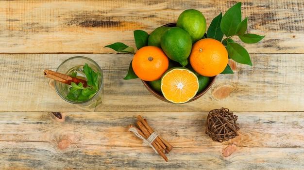 Bovenaanzicht van mandarijnen met kaneel en gefermenteerde drank op houten bord