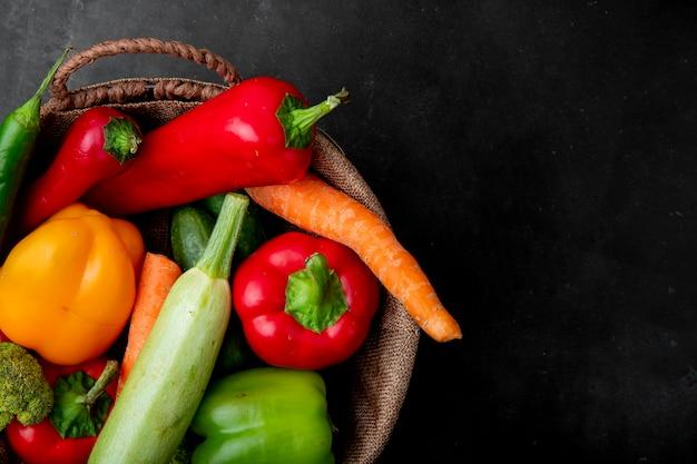 Bovenaanzicht van mandje van groenten aan de linkerkant en zwarte oppervlak