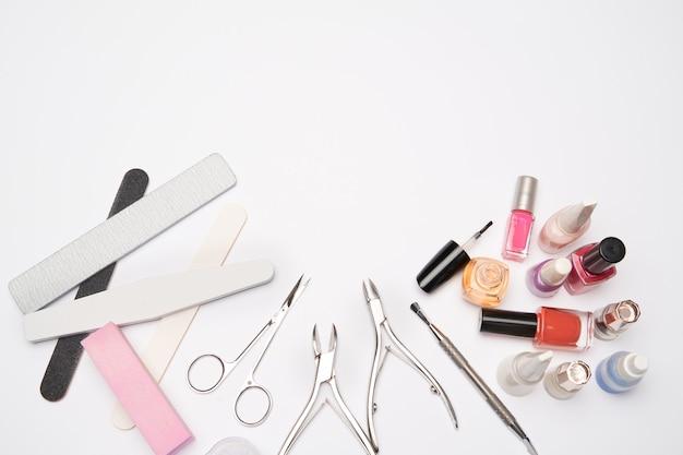 Bovenaanzicht van manicure tools voor nagelverzorging op lichte ondergrond - borstel, schaar, nagellak, vijl en pincet