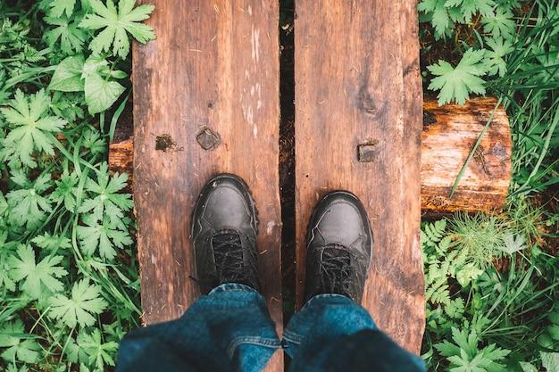 Bovenaanzicht van mannelijk schoeisel op een houten pad in een bos