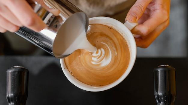 Bovenaanzicht van mannelijke barista melk gieten in koffiekopjes