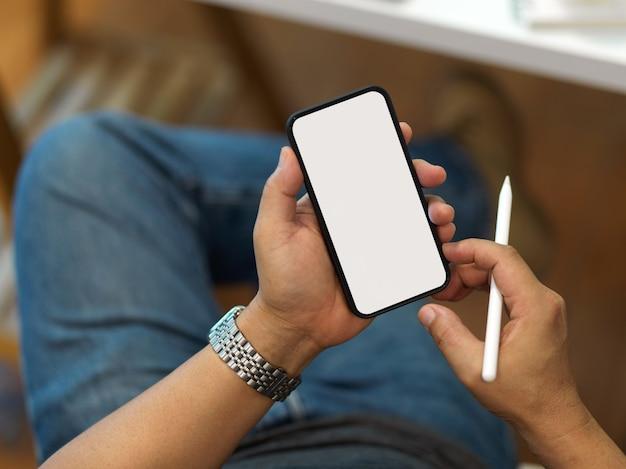 Bovenaanzicht van mannelijke bedrijfsmartphone omvatten uitknippadscherm en styluspen in zijn hand