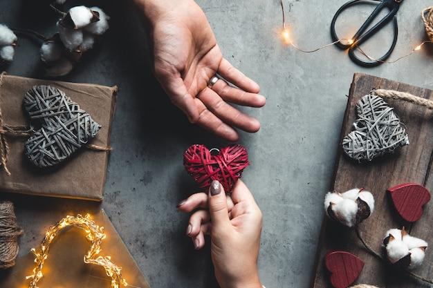 Bovenaanzicht van mannelijke en vrouwelijke handen met rode geschenkdoos met gouden lint op roze achtergrond plat leggen.