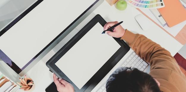 Bovenaanzicht van mannelijke grafisch ontwerper schetsen op tablet