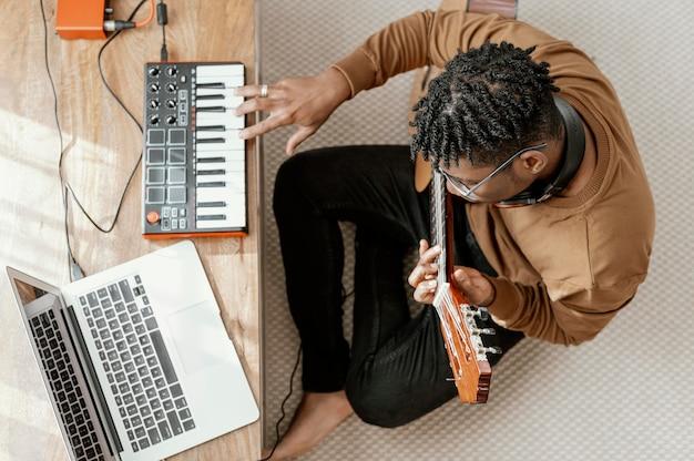 Bovenaanzicht van mannelijke muzikant thuis gitaar spelen en mengen met laptop