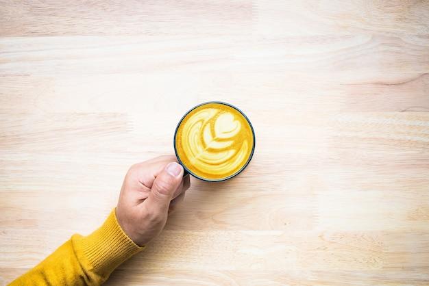 Bovenaanzicht van mannenhand met kopje koffie op hout