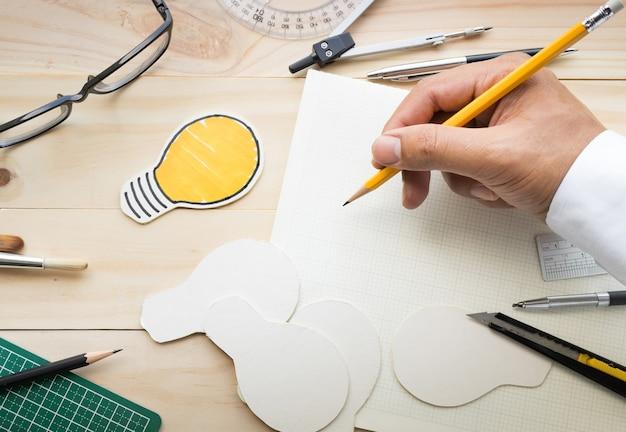 Bovenaanzicht van mannenhand op houten tafel met elementen van tools, apparatuur.