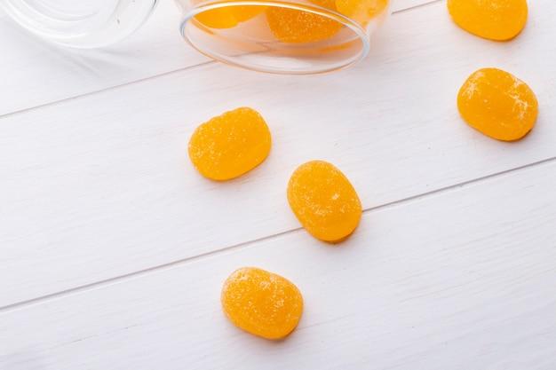Bovenaanzicht van marmelade snoepjes verspreid uit een glas op houten oppervlak