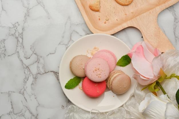 Bovenaanzicht van marmeren eettabla met een plaat van franse kleurrijke macarons versierd met rozenbloem