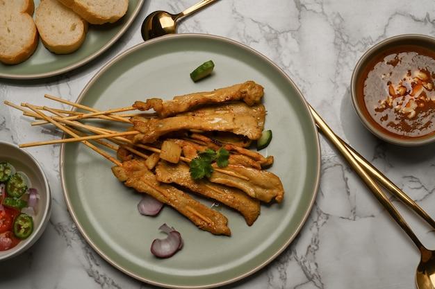 Bovenaanzicht van marmeren eettafel met gegrilde varkensvlees sata