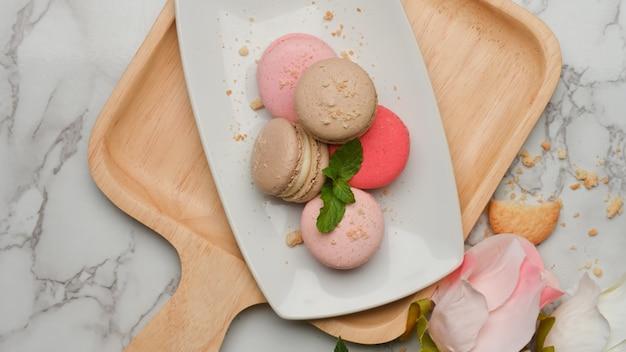 Bovenaanzicht van marmeren tafel met een plaat van franse kleurrijke macarons op houten dienblad versierd bloem