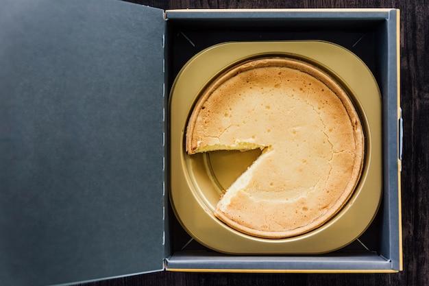 Bovenaanzicht van mascarpone crème brulee cheesecake met ontbrekende plak, zachte, rijke melkachtige smaak in papieren doos.