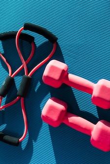 Bovenaanzicht van mat op vloer met rubberen expander en twee halters in fitnessclub geplaatst