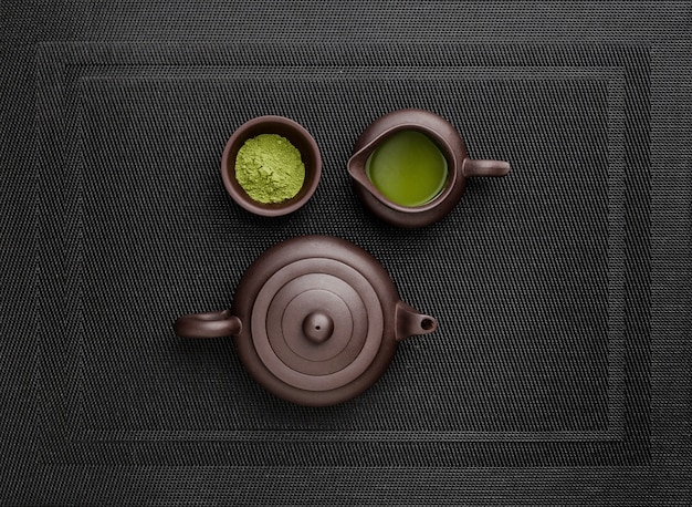 Bovenaanzicht van matcha-thee in theepot en poeder