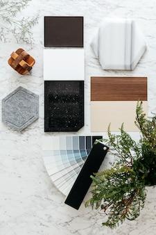 Bovenaanzicht van materiaalkeuzes inclusief graniettegel, marmertegel, akoestische tegel, walnoot en essenhout laminaat en geverfd kleurentoonalbum met plant en bloemen op marmeren tafel.