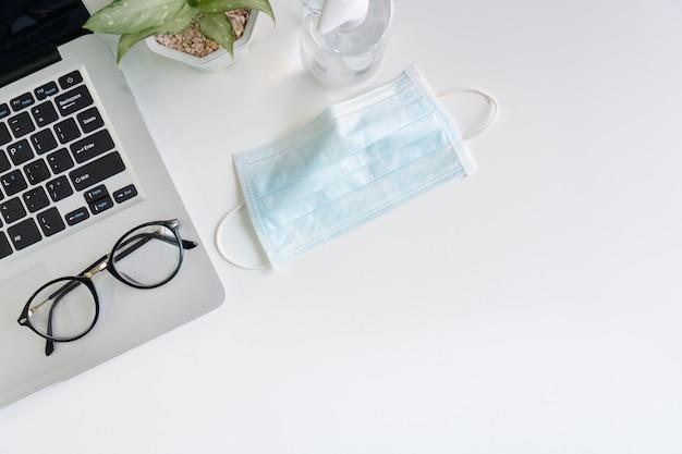 Bovenaanzicht van medisch gezichtsmasker en handdesinfecterend middel op bureau in kantoor