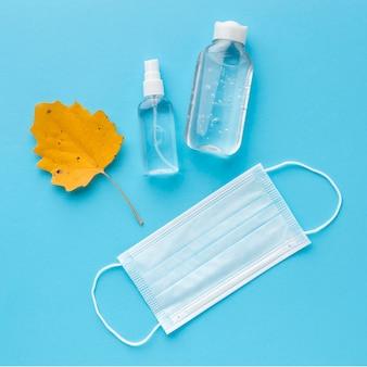Bovenaanzicht van medisch masker met handdesinfecterend middel en herfstblad
