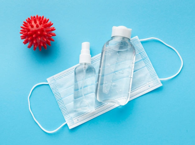 Bovenaanzicht van medisch masker met handdesinfecterend middel en virus