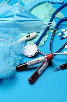 Bovenaanzicht van medische apparatuur en hulpmiddelen op blauwe ondergrond - stethoscoop, chirurgisch masker, medische handschoenen, spuit en bloed reageerbuis - gezondheidszorg en geneeskunde concept.