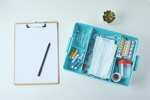 Bovenaanzicht van medische artikelen en leeg papier blanco vel op de witte achtergrond. gezondheidszorg en geneeskunde concept