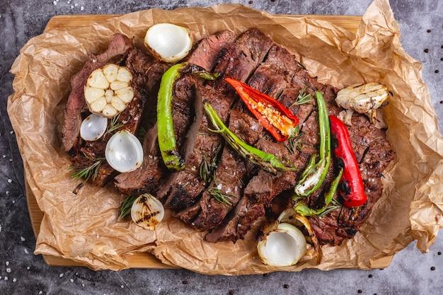 Bovenaanzicht van medium gekookt steak met knoflook, ui, rode peper en chili op perkamentpapier