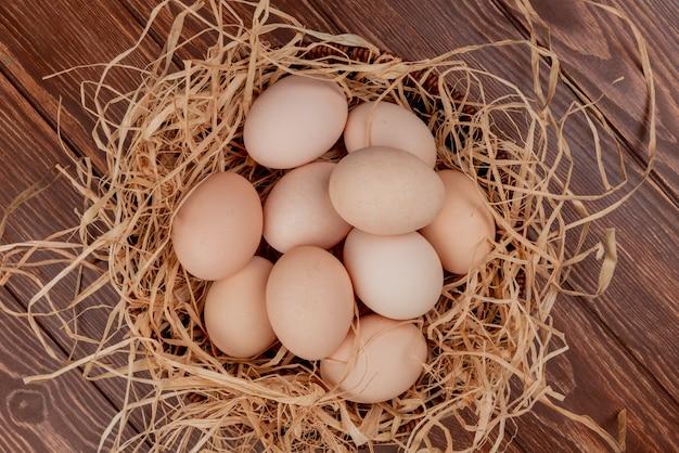 Bovenaanzicht van meerdere kippeneieren op nest op een houten achtergrond