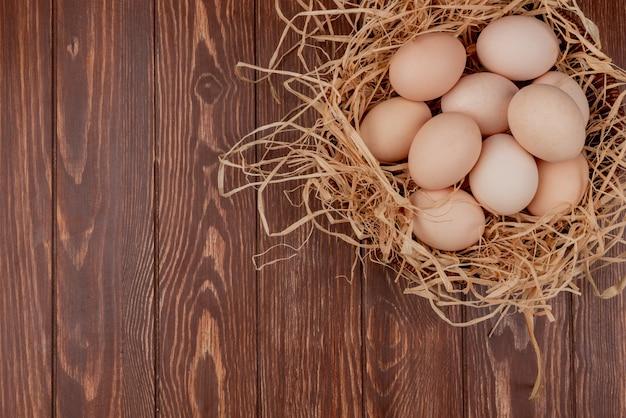 Bovenaanzicht van meerdere verse kippeneieren op nest op een houten achtergrond met kopie ruimte