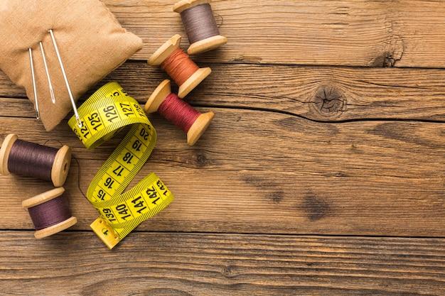 Bovenaanzicht van meetlint met draad en naalden