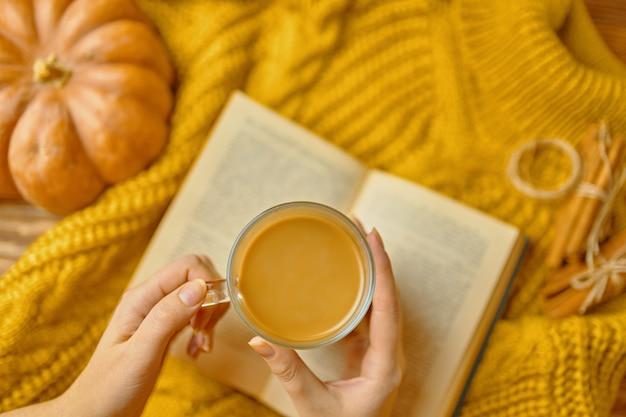 Bovenaanzicht van meisje hand op een tafel, een pompoen, kaneelstokjes, een boek op houten tafel.