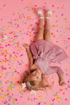Bovenaanzicht van meisje in sprookjeskostuum met confetti en toverstaf