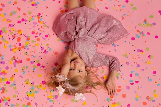 Bovenaanzicht van meisje in sprookjeskostuum met confetti