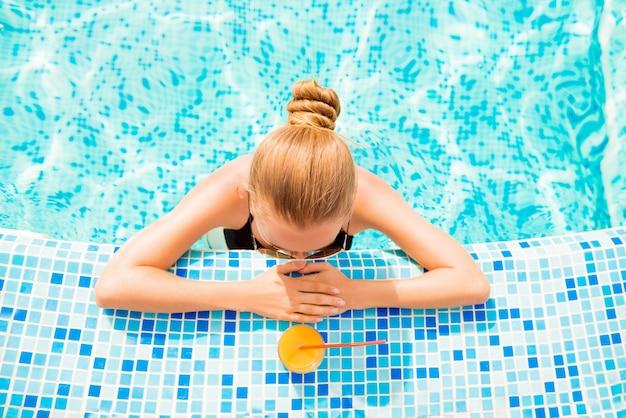 Bovenaanzicht van meisje zwemmen in een zwembad met sap en glazen