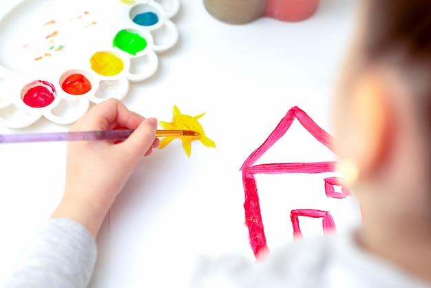 Bovenaanzicht van meisjeshand tekenen met penseelhuis en zon op wit papier.