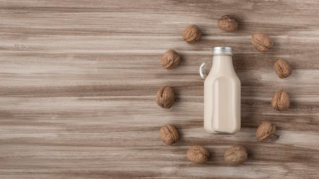 Bovenaanzicht van melkfles met walnoten en kopieer de ruimte
