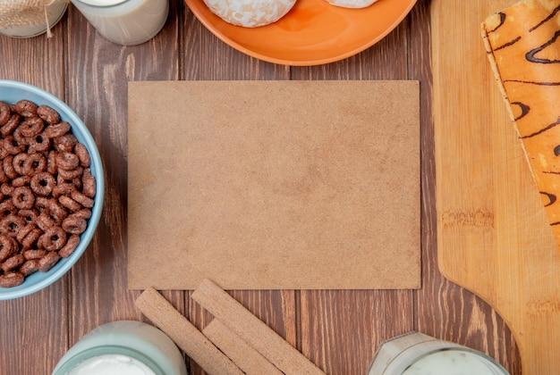 Bovenaanzicht van melkproducten als melk room zure geklonterde melk yoghurt soep met ontbijtgranen koekjes peperkoek en roll op snijplank rond karton op houten achtergrond met kopie ruimte