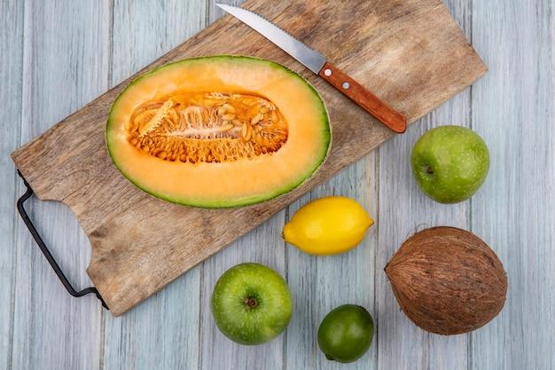 Bovenaanzicht van meloen plakjes meloen op houten keuken bord met mes met kokosnoot appels citroen op grijs hout
