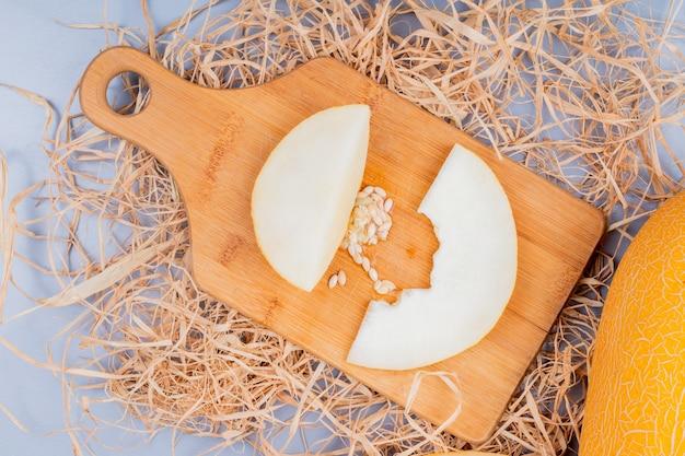 Bovenaanzicht van meloen segmenten en zaden op snijplank en hele op stro op grijze achtergrond