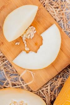 Bovenaanzicht van meloen segmenten en zaden op snijplank en snijd een op stro achtergrond