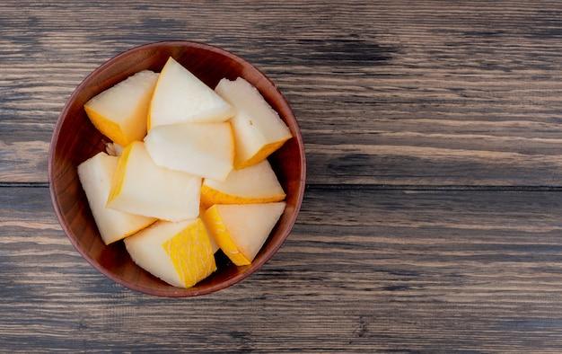 Bovenaanzicht van meloen segmenten in kom op houten achtergrond met kopie ruimte