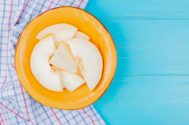 Bovenaanzicht van meloen segmenten in plaat op geruite doek en blauwe achtergrond met kopie ruimte