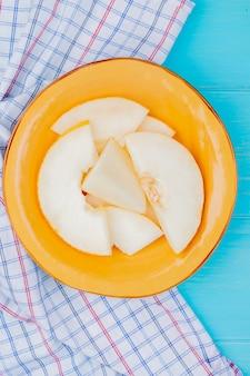 Bovenaanzicht van meloen segmenten in plaat op geruite doek en blauwe achtergrond
