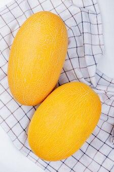 Bovenaanzicht van meloenen op geruite doek en witte achtergrond