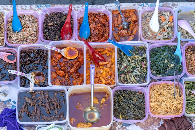 Bovenaanzicht van mensen die eten kopen boven verschillende heerlijke maleisische huisgemaakte gerechten die worden verkocht bij straatmarktkraam in kota kinabalu, eiland borneo, maleisië
